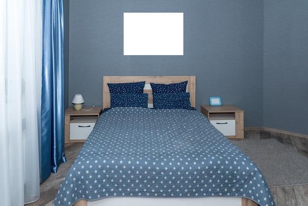 Interior com roupa de cama azul no sofá. quarto com cama, roupa de cama azul e mesa de cabeceira. almofadas azuis, capa de edredão cinza na cama com cabeceira de madeira. vista frontal.