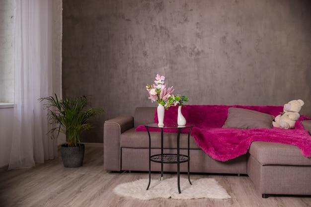 Interior com sofá. mesa redonda com buquê de flores.