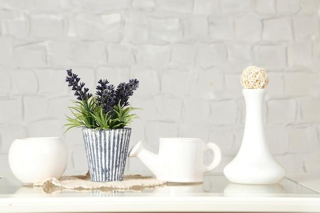 Interior com vasos decorativos e planta na mesa e fundo da parede de tijolo branco