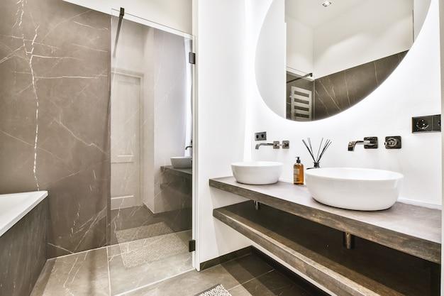 Interior contemporâneo de banheiro com chuveiro e pia de cerâmica
