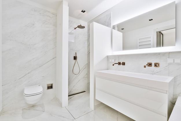 Interior contemporâneo de banheiro com chuveiro e toalete perto de pias de cerâmica branca em apartamento
