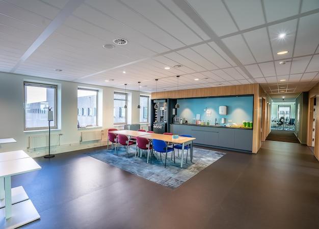 Interior da área da cozinha de um escritório moderno com uma longa mesa e cadeiras de madeira