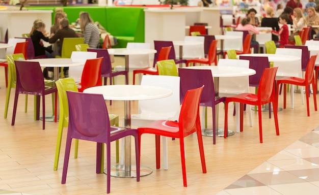 Interior da área de jantar pública com cadeiras e mesas de plástico colorido