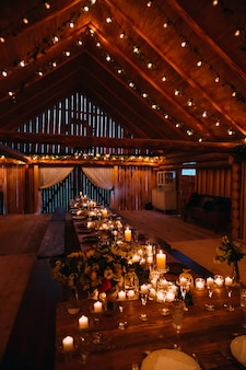 Interior da cabana de madeira e mesa conjunto iluminado por velas prontas para banquete de casamento