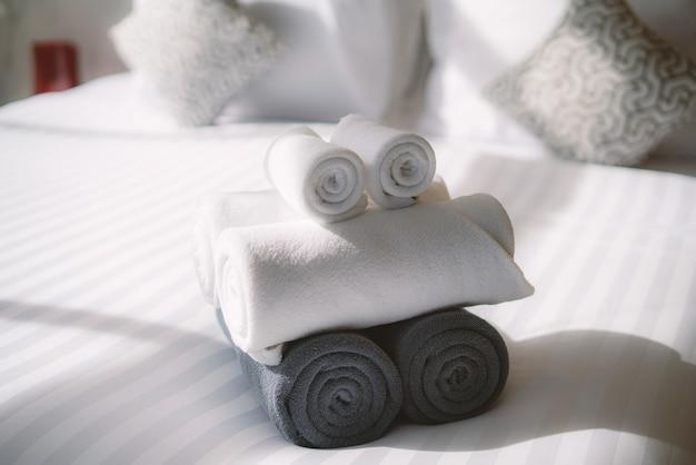 Interior da casa com rolo de toalhas brancas na cama no quarto