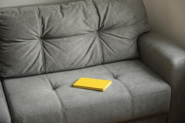 Interior da casa com sofá cinza e caderno amarelo