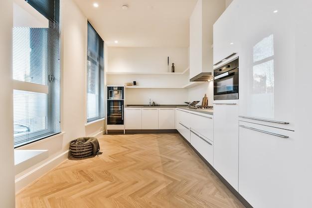 Interior da casa, cozinha, sala com armários minimalistas brancos e eletrodomésticos embutidos e passagem aberta para a sala de jantar com mesa