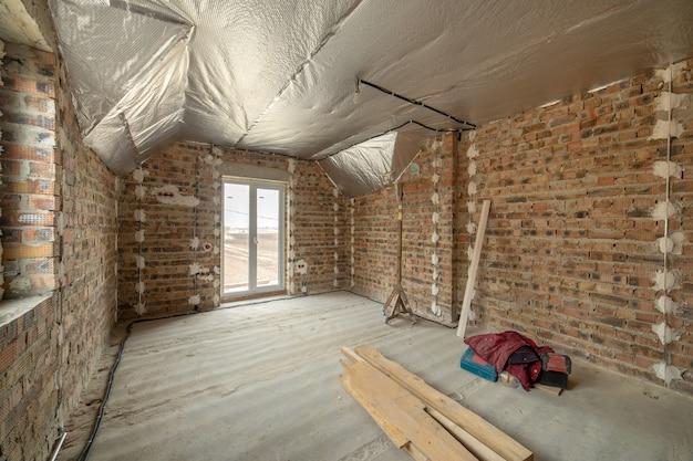 Interior da casa de tijolo inacabado com piso de concreto e paredes nuas prontas para reboco em construção. incorporação imobiliária
