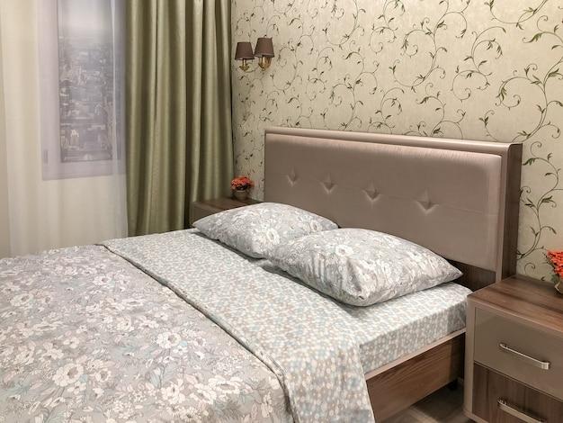 Interior da casa do quarto, cama bem feita com dois travesseiros e cobertor