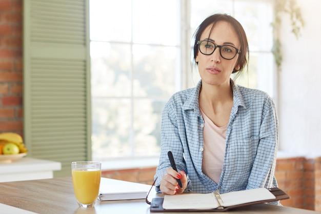 Interior da casa. mulher atraente usa roupas casuais, escreve o plano no diário, tem uma expressão pensativa