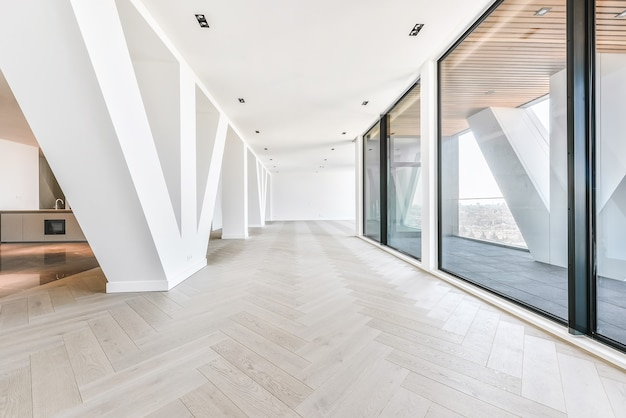 Interior da cobertura do estúdio com paredes de vidro e terraço com vista da cidade à luz do sol