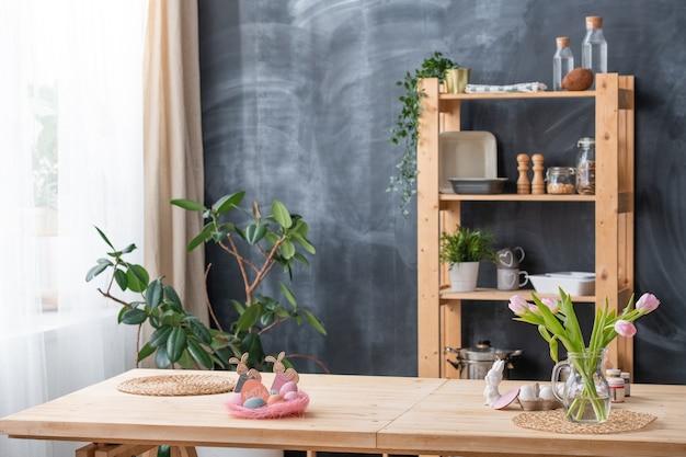 Interior da cozinha com decorações de páscoa e flores em um vaso na mesa, louças nas prateleiras contra o quadro-negro