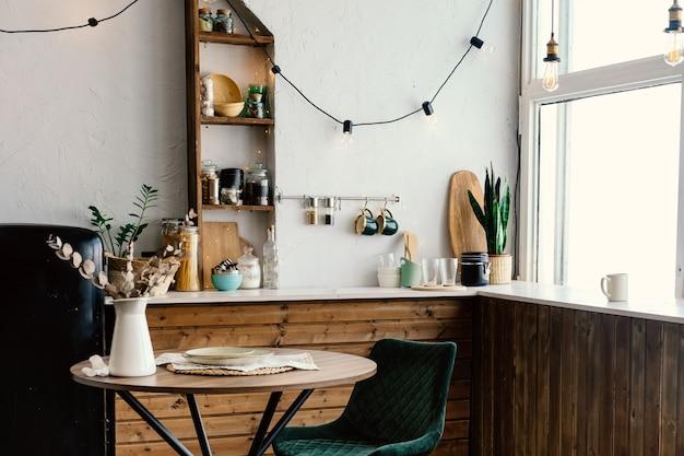Interior da cozinha com piso de madeira escura. grande janela na cozinha. interior da primavera
