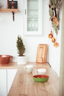 Interior da cozinha doméstica com duas canecas brancas e prato de cerâmica
