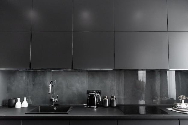 Interior da cozinha elegante nas cores cinza e preto