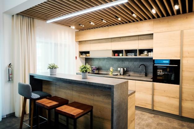 Interior da cozinha em apartamento grande e confortável ou casa de campo com forno instalado entre os armários, cadeiras, mesa e outros móveis