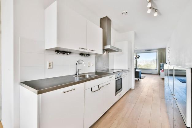 Interior da cozinha leve com armários modernos e eletrodomésticos localizados perto da sala de jantar em um apartamento moderno durante o dia