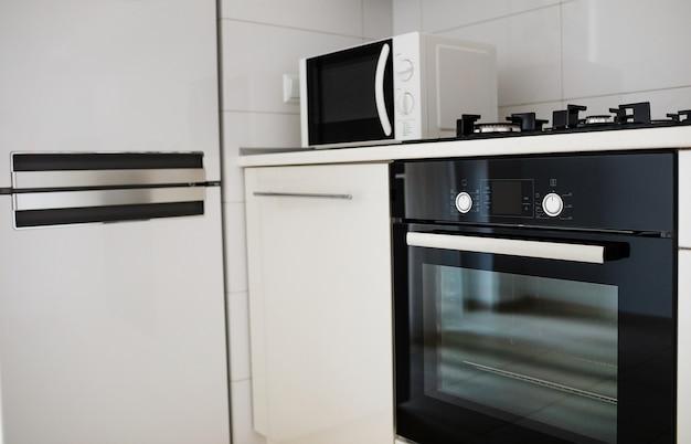 Interior da cozinha moderna com fogão elétrico e forno microondas