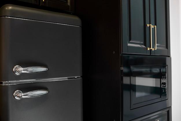 Interior da cozinha moderna com geladeira. geladeira preta retrô.