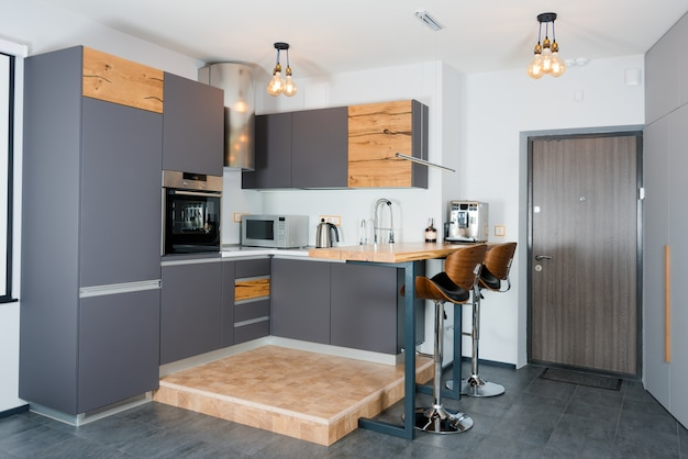 Interior da cozinha moderna com luzes na mesa de madeira marrom e bancos de barra, máquina de café. interior contemporâneo com elementos loft