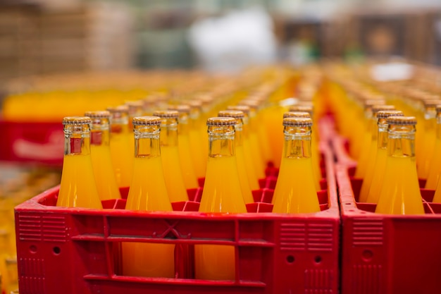 Interior da fábrica de bebidas. transportador que flui com garrafas de suco ou água.