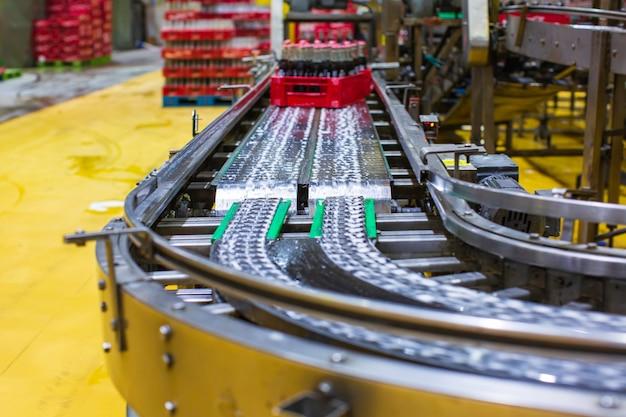 Interior da fábrica de bebidas. transportador que flui com garrafas para água gaseificada.
