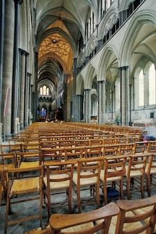 Interior da igreja ornamentada cheia de cadeiras de madeira