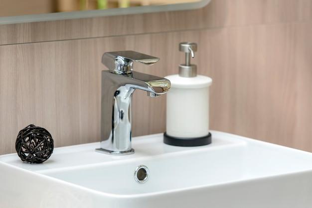 Interior da moderna casa de banho com pia branca e torneira, pia close-up