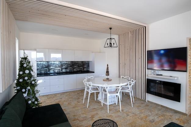 Interior da moderna cozinha espaçosa, com paredes brancas, elementos decorativos de madeira, móveis contemporâneos e grande sofá macio.