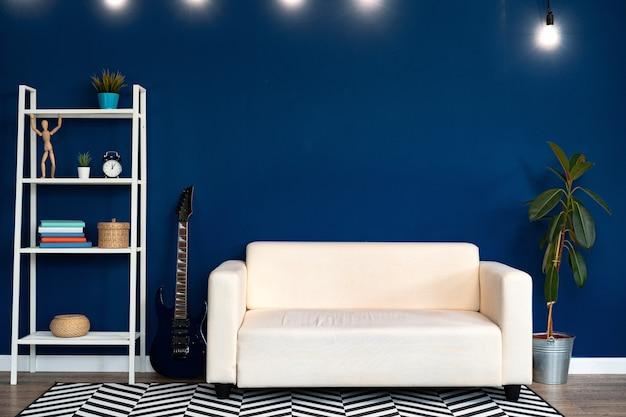 Interior da moderna sala de estar com sofá branco contra a parede azul