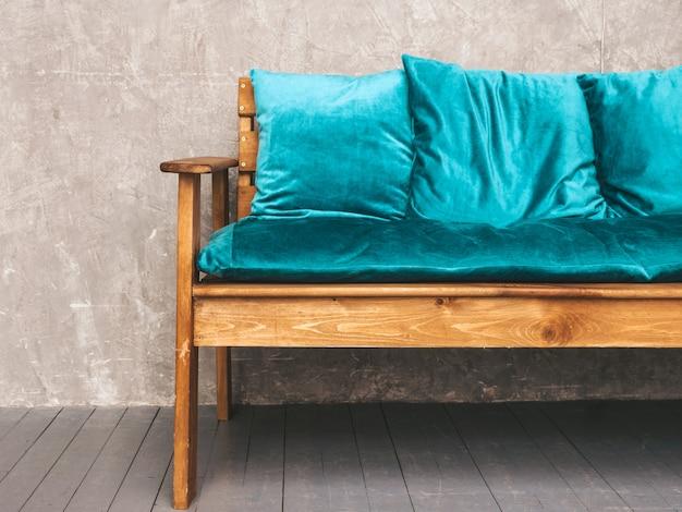 Interior da parede cinza com elegante sofá moderno estofado em azul e madeira, luminárias penduradas