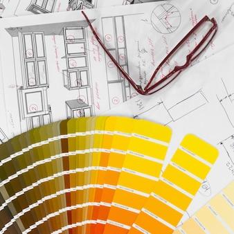 Interior da planta arquitetônica com amostras de madeira e papel e uma paleta multicolorida e ferramentas de desenho