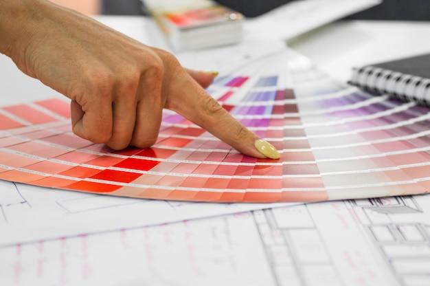 Interior da planta arquitetônica com amostras de papel e uma paleta multicolorida e ferramentas de desenho