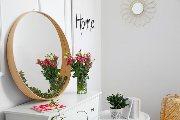 Interior da sala com espelho elegante e flores primaveris