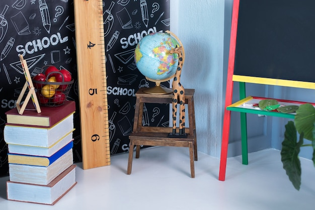 Interior da sala de aula. de volta à escola. sala de aula vazia com quadro negro e livros, globo.