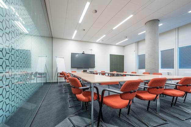Interior da sala de conferências de um escritório moderno com paredes brancas e um monitor
