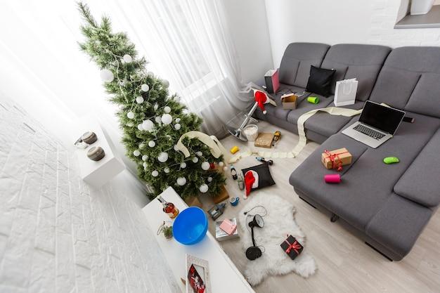 Interior da sala de estar bagunçado com árvore de natal. caos depois da festa