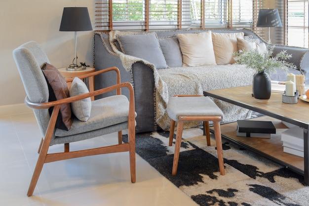 Interior da sala de estar com almofadas no sofá e mesa de madeira decorativa com lâmpada