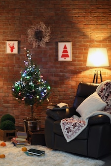 Interior da sala de estar com poltrona preta, abajur e árvore de natal na parede de tijolos