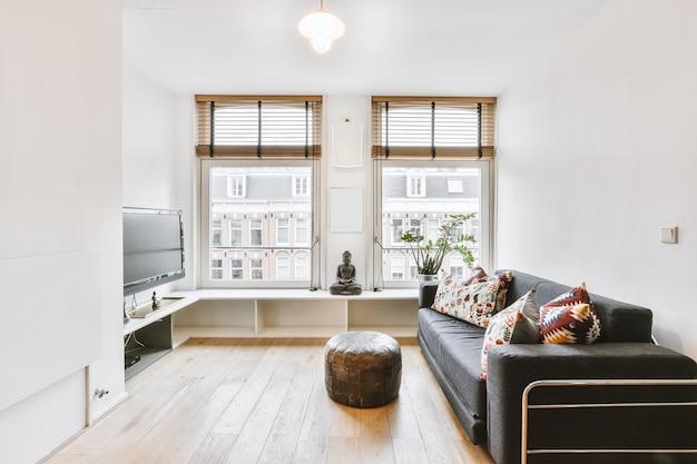 Interior da sala de estar com sofá confortável e tv contra janelas em apartamento contemporâneo