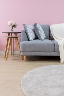Interior da sala de estar com sofá de veludo cinza na parede rosa