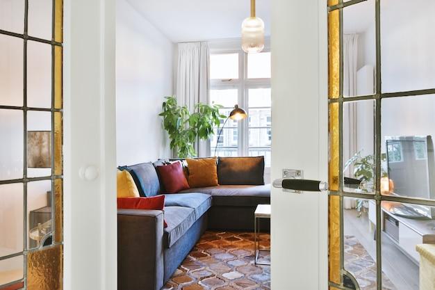 Interior da sala de estar contemporânea com sofá com almofadas macias e luminária de chão em apartamento