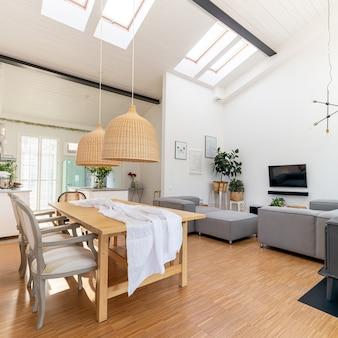 Interior da sala de estar e jantar em plano aberto com tv plana, sofá cinza e mesa de madeira com cadeiras modernas