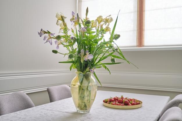 Interior da sala de jantar em casa, buquê de primavera verão de flores, morangos
