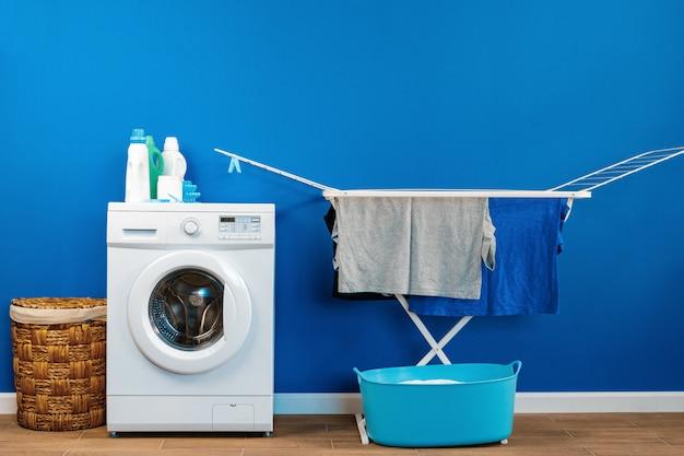 Interior da sala de lavanderia com máquina de lavar e secadora de roupas perto da parede