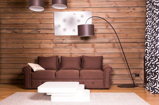 Interior da sala de madeira com sofá e mesa