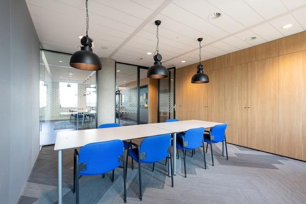 Interior da sala de reuniões de um escritório moderno com uma longa mesa de madeira e cadeiras ao redor