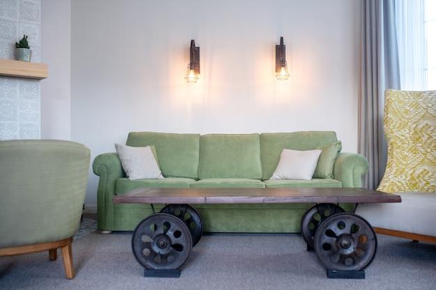 Interior da sala. sofá verde macio e confortável com almofadas e mesa baixa de madeira com rodas grandes em sala com lâmpadas de parede