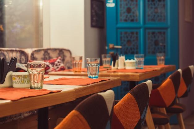 Interior da sala vazia nas cores azuis e laranja, mesa e cadeiras servidas