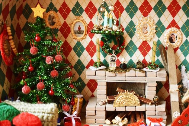 Interior de ano novo na casa de brinquedo. sala com lareira e árvore de natal para bonecas e brinquedos pequenos